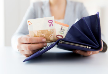 close up of woman hands with wallet and euro money