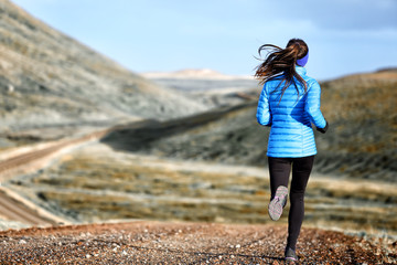 Woman winter and autumn running in down jacket