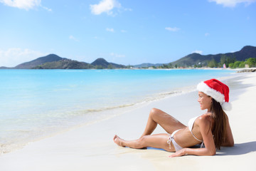 Wall Mural - Christmas beach woman in santa hat on holidays