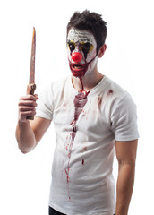 Portrait of an evil clown holding a knife over white background