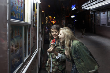 Two young women sharing an ice cream