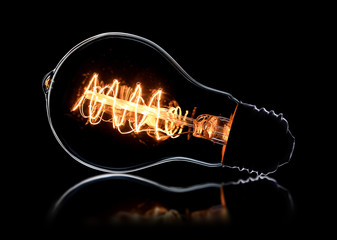 Glowing vintage light bulb on black