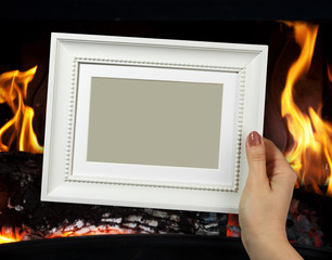 Wooden frame in woman hands on the background of fire