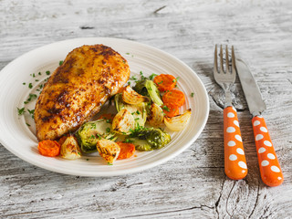 baked chicken breast with brussels sprouts, onions and carrots on a white plate on wooden surface. Healthy food