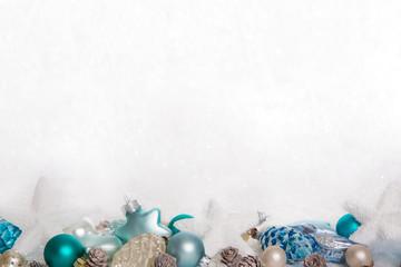 Dekoration zu Weihnachten in blau, türkis und weiß auf Schnee Hintergrund.
