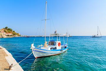 White and blue color Greek fishing boat mooring in Kokkari port, Samos island, Greece