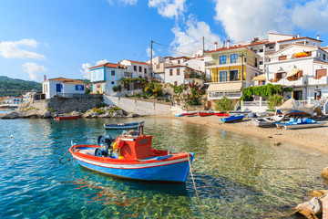 Fishing boat in Kokkari bay with colourful houses in background, Samos island, Greece