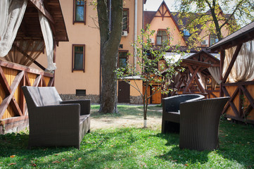 brown leather sofa and two chairs in the garden near the house