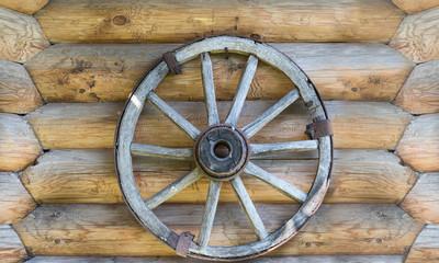 Cart wheel on log wall