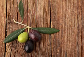 Fototapete - Tre olive su un tavolo di legno