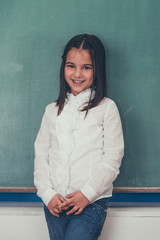 Color, old fashioned portrait of beautiful little girl standing in front of school chalkboard and smiling. Photo is carefully post processed for achieving finest film look.