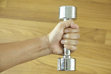 Stock Photo:.Hand holding steel dumbbell on wooden background