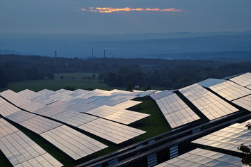 Solar power station at dusk. Industrial landscape with factory chimneys and forested mountains fading into the misty haze in the background. View from above.