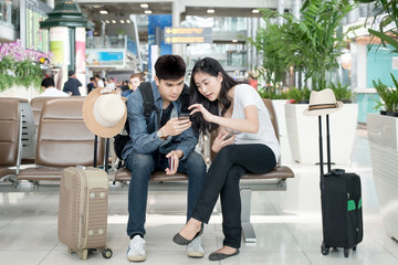 Young Asian couple using smart phone while sitting in the airpor