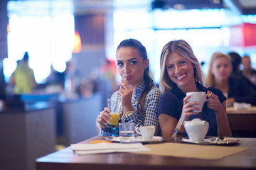 girls have cup of coffee in restaurant