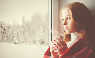 Pensive sad girl with a warming drink looking out the window in