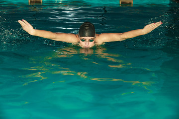 Woman athlete swimming in pool.