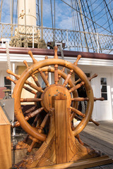 Ships steering wheel on old wooden ship