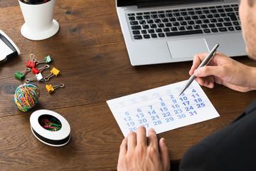 Fototapete - Businessperson Holding Pen Over Calendar