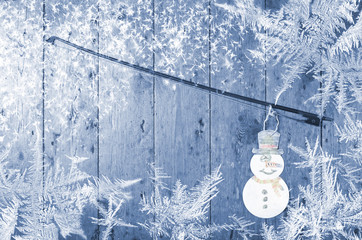 Snowman attached to the violin bow, blue, wooden  background. Winter time snowflakes around.