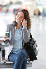 Young attractive business woman using smartphone drinking coffee