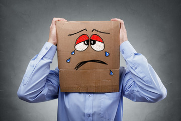 Man with cardboard box on his head showing sad expression
