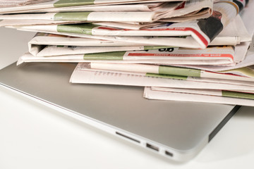 Stack of newspapers, placed on a laptop