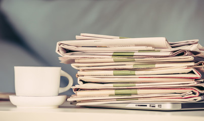 Stack of newspapers with a cup of coffee