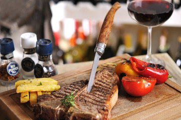T-Bone steak barbecue with fried potato and red wine on wood table
