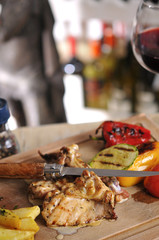 Chicken barbecue with fried potato and red wine on wood table