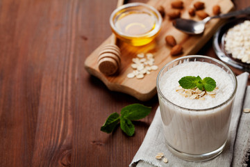 Healthy breakfast of banana smoothie or milkshake with oats and honey decorated mint leaves on rustic surface