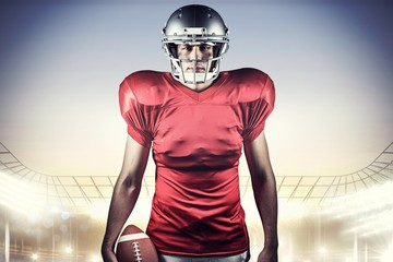 Composite image of american football player holding ball