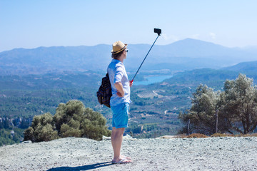 Tourist making self against the backdrop of beautiful scenery