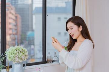 歯磨きをしながら携帯電話を操作するパジャマ姿の女性