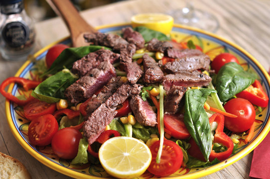 Seasonal salad with beef and red wine on wooden table