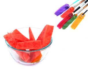 Colors variety / Watermelon sliced, green knife and art brushes with acrylic paints on a white background