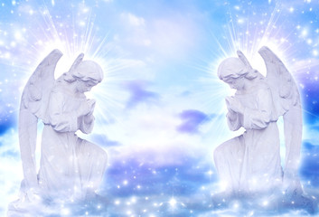 two praying angels with rays of light over blue sky with stars