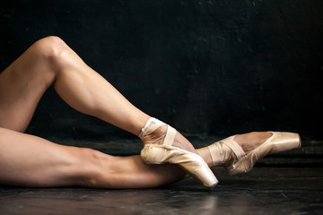 Close-up ballerina's legs in pointes on the black wooden floor