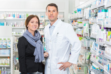 Confident Pharmacist Standing With Customer In Pharmacy