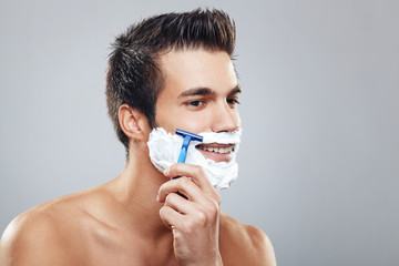 Young man shaving beard