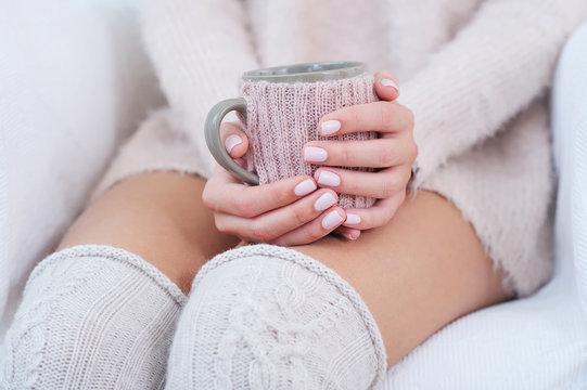 Closeup woman hands with delicate pink manicure holding decorated cup; knitted knee socks on woman legs