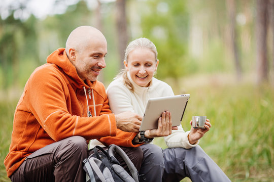 Couple of backpackers looking on tablet computer