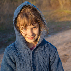 Little girl smiling looks at camera while a walk in the autumn p