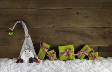 Wichtelmann als Santa mit Weihnachtsgeschenke in rot grün auf Holz Hintergrund.