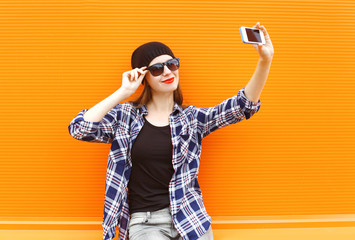 Fashion pretty cool girl makes selfie portrait on smartphone ove