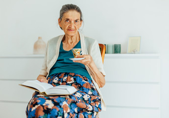 Old woman with a cup of tea and a book