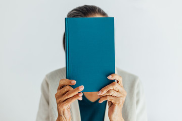 Old woman holds a turquoise book with copy space