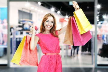Beautiful young woman with shopping bags in the mall