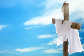 Cross with crown of thorns and cloth on sky background