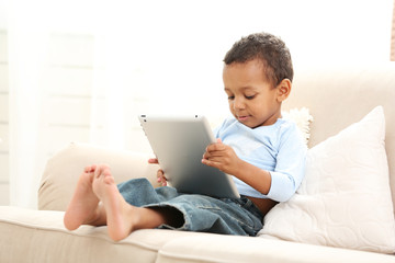 Little boy sitting on sofa with tablet in the room
